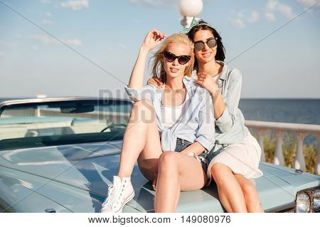 Two gorgeous young women sitting on car in summer