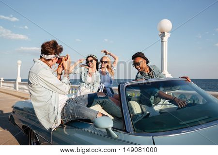 Group of beautiful young people driving cabriolet and talking photos in summer