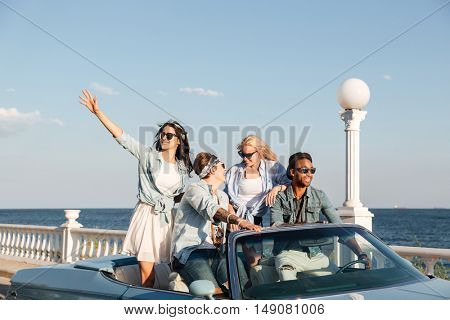 Group of happy young people laughing and driving car