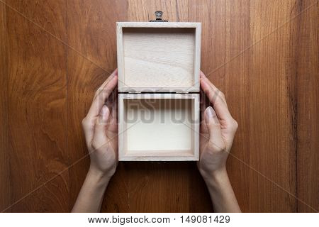 A woman two hands hold a empty(blank) opened wooden box with hinge for accessory top view studio.