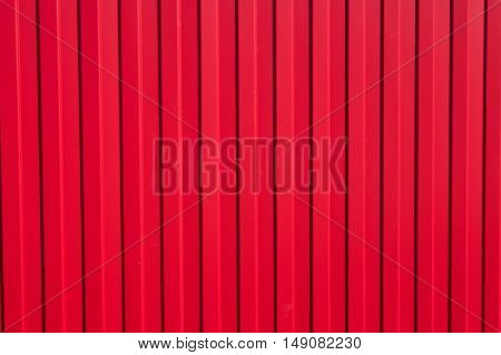 Iron fence with bright red ribs and cogs. Abstract background or texture in bright sunlight.