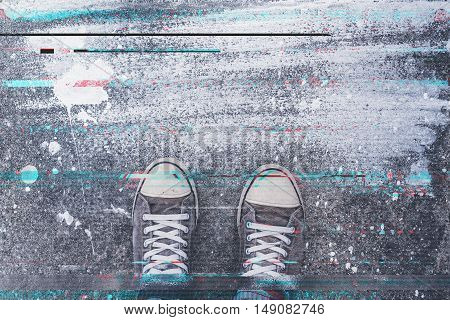 Pair of sneakers on pavement with digital glitch effect young adult man standing on concrete flooring