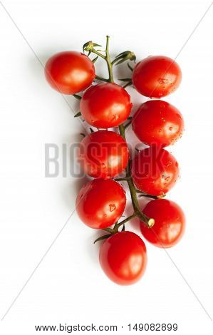 Sprig of cherry tomatoes isolated on a white background. Space for text. The concept of healthy nutrition, organic food, fresh vegetables, veganism