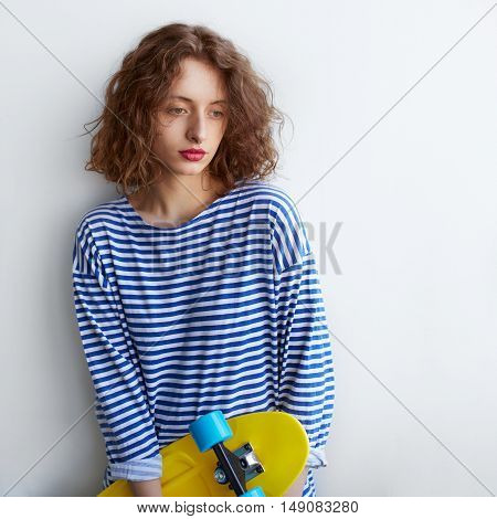 pretty sad hipster girl holding a skateboard on white background with copy space. Curly hairstyle young woman leaning against a wall thoughtful and looking down.