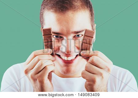 Portrait of young handsome man holding chocolate bar