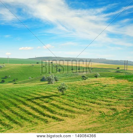Hilly terrain with a terrace and a blue sky with clouds.