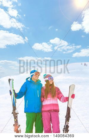 Smiling couple with skis outdoors