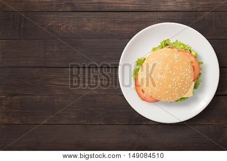 Top view BBQ burger on white dish on wooden background. Copy space for your text.