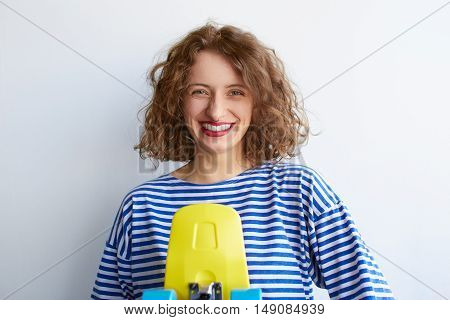 portrait of beautiful happy cute brunette woman in casual hipster summer clothes with bright make up posing over white wall with yellow skateboard
