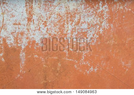 Plastered scratched wall with peeling paint in biue and pink colors
