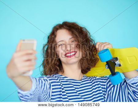 Beautiful smiling young woman with bright yellow skateboard taking self-portrait picture on smartphone on blue turqoise colorful backgroud. Hipster girl with curly hair making a selfie with pennyboard