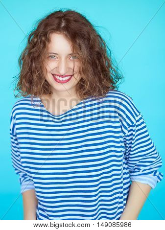 Vertical portrait of a smiling beautiful brunette woman with clean make up over bright colorful blue background. Alternative hipster girl over vibrant color wall