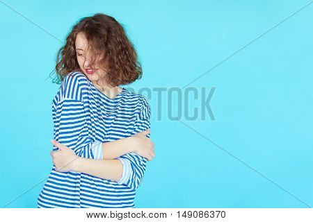 Fashion portrait of a stylish girl in marine style over bright blue turquoise color background with content blank space.