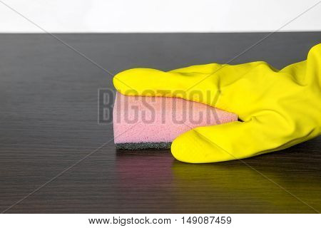 cleaning table in mittens. Colors pink sponge