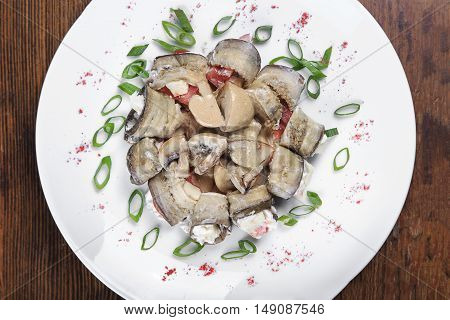 on the table a plate of rolls baked eggplant with tomatoes cheese mushrooms onions. top view
