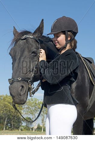 young girl with a black stallion in a field