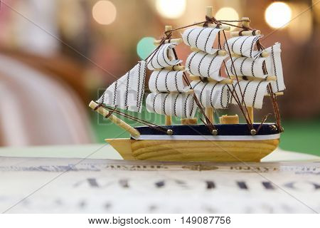 children's sailing vessel made of wood. The background is blurred