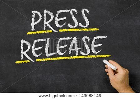 Press Release written on a dark blackboard