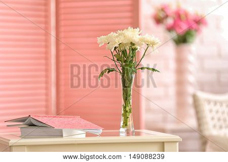 Vase with flowers and books on white table