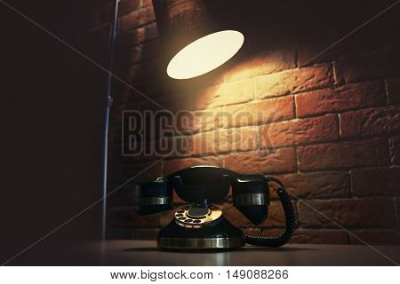 Old telephone on the table in dark room