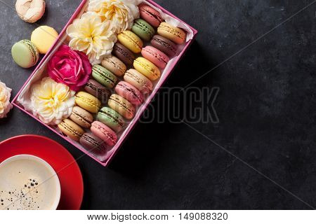 Colorful macaroons and coffee on stone table. Sweet macarons in gift box and flowers. Top view with copy space