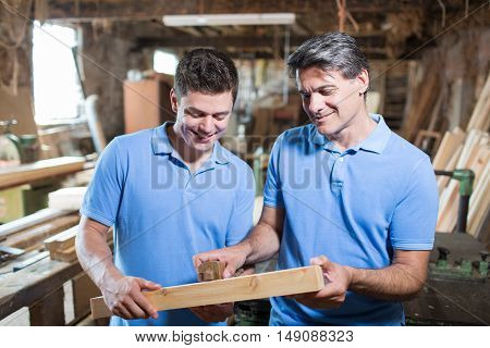 Carpenter Teaching Apprentice How To Measure Wood