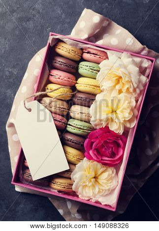 Colorful macaroons and flowers on stone table. Sweet macarons in gift box. Top view. Toned