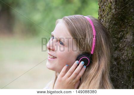 Girl Sitting Against Tree In Garden Listening To Music On Headphones