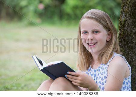Girl Sitting Against Tree In Garden Reading Book