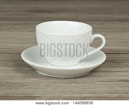 White mug and saucer on a wooden background