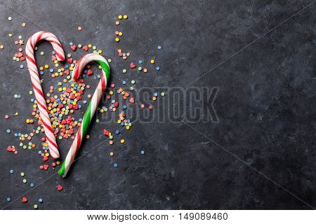 Candy canes over stone background. Top view with copy space