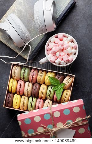 Colorful macaroons in a gift box and headphones on stone table. Sweet macarons. Top view