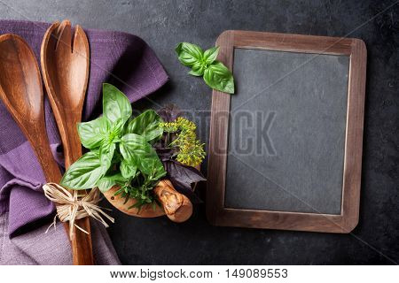 Blackboard for your text, fresh garden herbs in mortar on stone table. Basil, rosemary, dill. Cooking ingredients. Top view with copy space