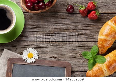 Blackboard, croissants, berries, flowers and coffee cup. Top view with copy space