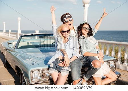 Cheerful young man and two women standing with raised hands near vintage cabriolet