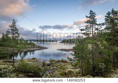 Ladoga lake bay and small islands at sunset warm light. Nature of Karelia republic, Russia.