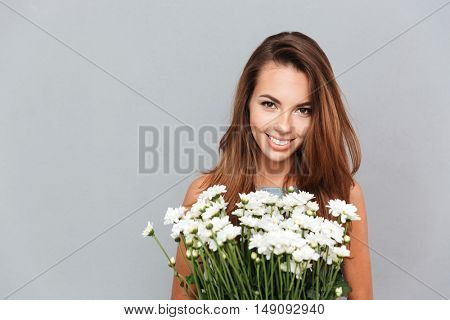 Closeup of cheerful attractive young woman with bunch of flowers over grey background