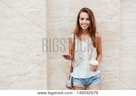 Cheerful young woman holding smartphone and coffee cup and looking at camera outdoors
