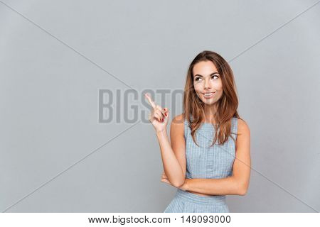 Happy beautiful young woman pointing away over grey background