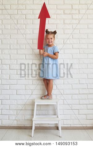 Little girl in a light-blue dress holds an arrow, showing it and smiling. Standing on a chair against a white brick wall