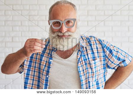 Happy stylish senior dressed in checkered shirt and trying grey paper glasses, white brick wall in background