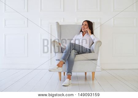 Female talking on the smart phone while sitting on the floor. She is rather relaxed and dreaming while talking