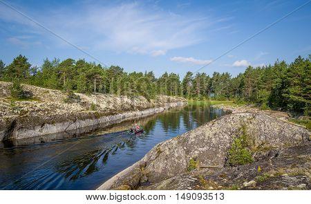 Small Inflatable fishing boat at Karelia island bay on Ladoga lake.