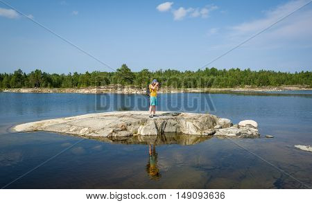 Tourist is taking pictures standing at small stone island on the Ladoga lake. Karelia republic, Russia.