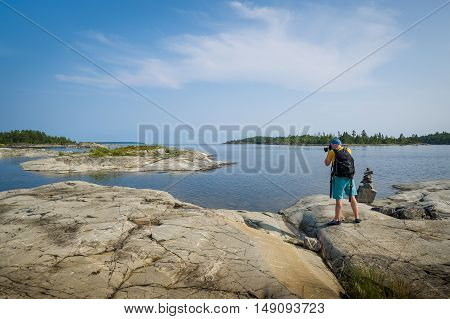 Tourist photographer with black photo backpack is taking pictures standing at stone island on the Ladoga lake. Karelia republic, Russia.