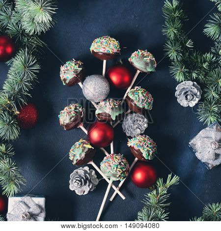 Blue spruce branches with christmas baubles and cake pops with colored sprinkles on green frosting on dark black concrete effect background. Square image