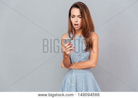 Upset amazed young woman listening to music and using mobile phone over grey background