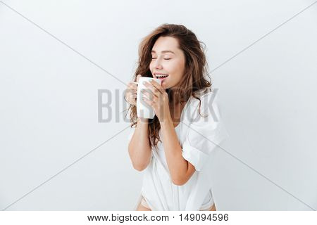 Happy attractive woman with eyes closed drinking cup of tea isolated over white background