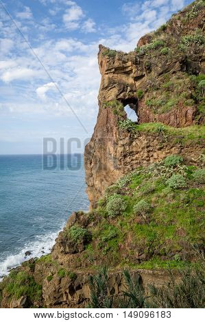 Vertical photo of Madeira island rocky shores with cave in the mountain, Ponta do Sol, Madeira, Portugal.
