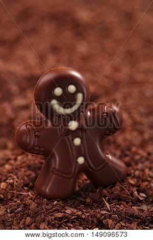 dark chocolate gingerbread man on chocolate flakes background